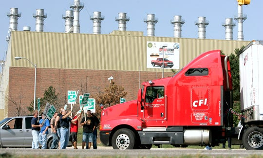 UAW workers stand in front of a semi-truck that is trying to drive onto GM grounds in 2007.