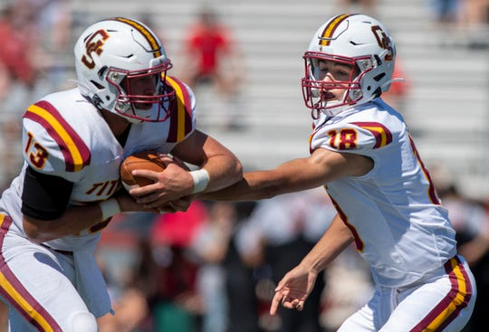 Gibson Southern High School sophomore Brady Allen (18) hands the ball off to teammate senior Mitchell Spindler (13) during the first half of action in an IHSAA varsity football game at Southport High School in Indianapolis, Tuesday, Sept. 10, 2019.