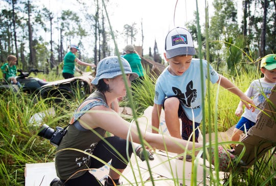 Bryson Whittamore, 6, helps, volunteers prepare six acres of land belonging to Temple Beth El in south Fort Myers — for the planting of hundreds of native trees on Saturday. The new Temple Preserve & Memorial Gardens will be located alongside the Crown Colony golf course and the Stonebridge neighborhood. OneTree.org, a local nonprofit, led the effort.