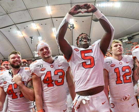 Clemson defensive end K.J. Henry(5) holds up a heart with his hands for the alma mater after the game at the Carrier Dome in Syracuse, New York, Saturday, September 14, 2019.
