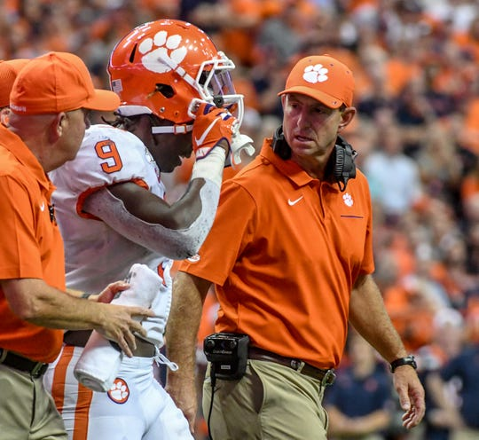 "Clemson Head Coach Dabo Swinney checks on running back Travis Etienne (9) after getting a ""stinger"" during the first quarter at the Carrier Dome in Syracuse, New York, Saturday, September 14, 2019."