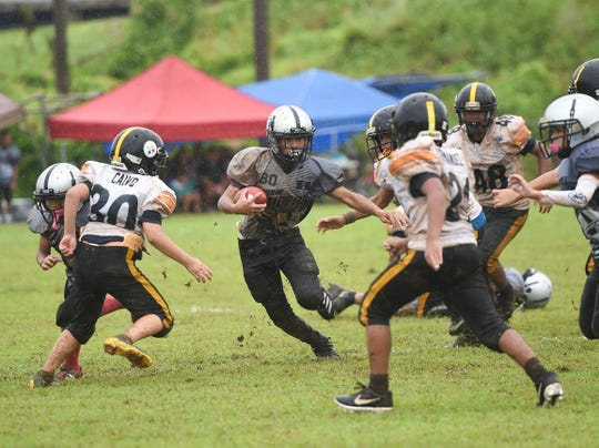 The Guam Raiders' Tristan Jay Burgos (80) rushes the ball against the Tamuning Steelers during a GNYFF Metgot division game at Tamuning Field in this Sept. 15, file photo.