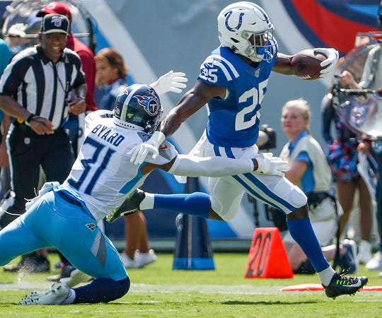Indianapolis Colts running back Marlon Mack (25) stiff arms Tennessee Titans free safety Kevin Byard (31) as he runs out of bounds in the first quarter of their game at Nissan Stadium in Nashville, Tenn., on Sunday, Sept. 15, 2019.