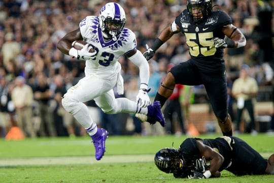 Texas Christian University running back Sewo Olonilua (33) runs the ball after leaping over Purdue linebacker Jaylan Alexander (36) during the first quarter of a NCAA football game, Saturday, Sept. 14, 2019 at Ross-Ade Stadium in West Lafayette. Texas Christian University won, 34-13.