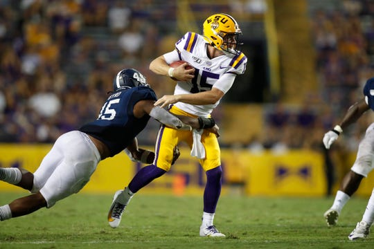 LSU quarterback Myles Brennan (15) runs past Georgia Southern linebacker Rashad Byrd (45) during an NCAA football game, Saturday, August 31, 2019, in Baton Rouge, La. (AP Photo/Tyler Kaufman)