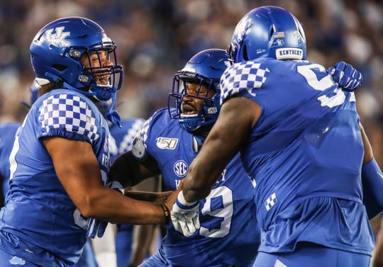 Kentucky defense players Isaiah Gibson,  Kordell Looney, center, and Calvin Taylor, Jr. celebrate a fumble recovery by the Cats against Florida. Sept. 14, 2019.