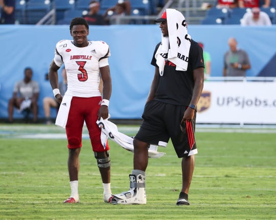 U of L QB's Malik Cunningham (3), left, and Jawon Pass (4) chatted as Evan Conley (6) took snaps against WKU at Nissan Stadium in Nashville.Sept. 14, 2019