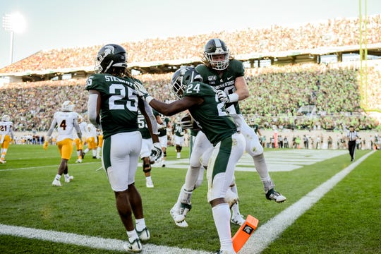 Michigan State's Elijah Collins, center, celebrates his touchdown with teammates Darrell Stewart Jr., left, and Matt Seybert Arizona State's during the third quarter on Saturday, Sept. 14, 2019, in East Lansing.