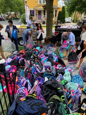 Jodi Kleibel's family and friends sort through over 1,000 backpacks that are going to be donated to kindergartners in need.