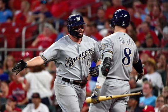 Brewers third baseman Mike Moustakas is greeted by left fielder Ryan Braun  after hitting a two-run home run.