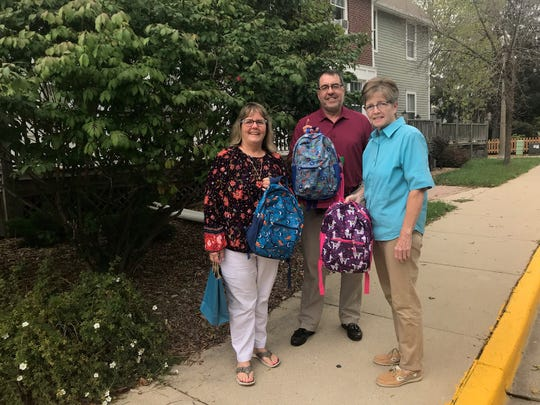Donna (left) and Jerry Gunderson and Judy Spiegel walk to Jodi Kleibel's celebration of life with kindergarten backpacks in hand to donate to kids in need.