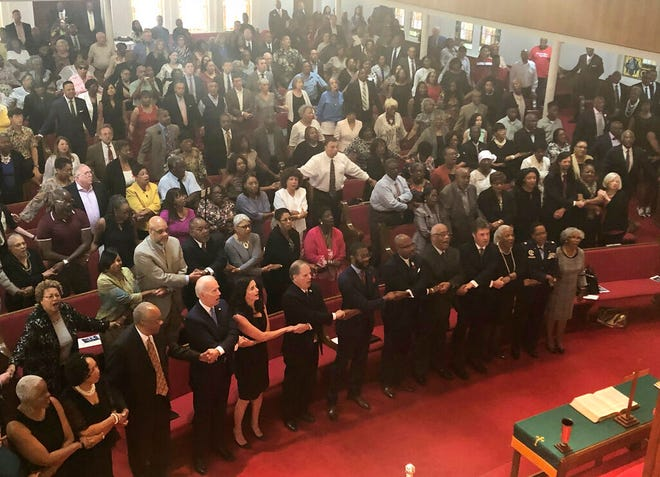 """Presidential candidate and former Vice President Joe Biden, left front, joins the congregation of 16th Street Baptist Church in Birmingham, Alabama, as they sing """"We Shall Overcome"""" at Sunday worship on Sept. 15, 2019. Biden was the keynote speaker as the congregation commemorated the 56th anniversary of the Ku Klux Klan bombing that killed four black girls in the congregation during the height of the civil rights movement. Biden is on the front pew along with Alabama Sen. Doug Jones, who as a federal prosecutor decades after the bombings prosecuted two of the responsible Klansmen, and Birmingham Mayor Randall Woodfin."""