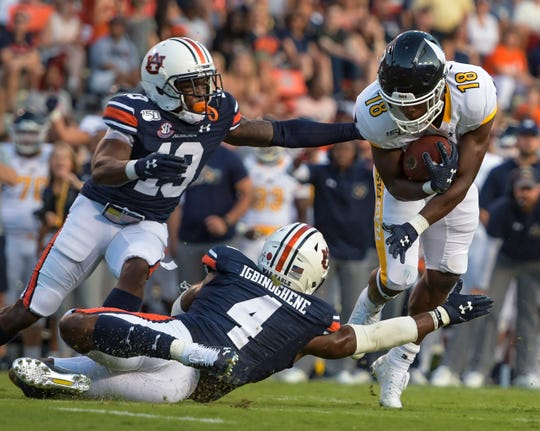 Auburn cornerbacks Javaris Davis (13) and Noah Igbinoghene (4) stop Kent State running back Xavier Williams (18) at Jordan-Hare Stadium on Sept. 14, 2019.