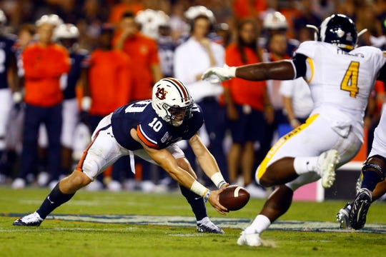 Auburn quarterback Bo Nix (10) bobbles the snap as Kent State linebacker Cepeda Phillips (4) applies pressure during the first half of an NCAA college football game Saturday, Sept. 14, 2019, in Auburn, Ala. (AP Photo/Butch Dill)