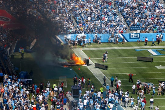 An item used in the introduction for players catches fire and burns on the sidelines during the opening ceremony at Nissan Stadium Sunday, Sept. 15, 2019 in Nashville, Tenn.
