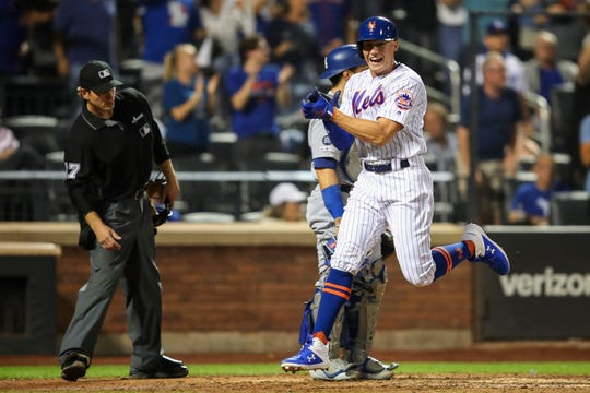 New York Mets' Brandon Nimmo scores on a three-run double pinch hit by Rajai Davis during the eighth inning of a baseball game against the Los Angeles Dodgers, Saturday, Sept. 14, 2019, in New York.
