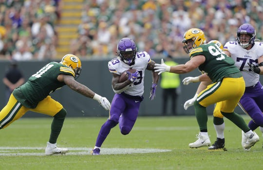 Minnesota Vikings running back Dalvin Cook (33) runs for a gain against Green Bay Packers outside linebacker Preston Smith (91) and Dean Lowry (94) in the third quarter during their football game Sunday, September 15, 2019, at Lambeau Field in Green Bay, Wis.