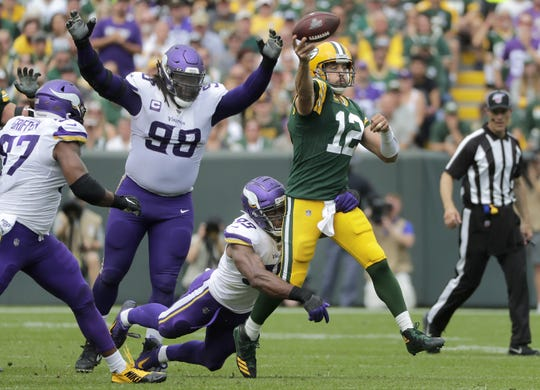 Green Bay Packers quarterback Aaron Rodgers (12) avoids a sack while under pressure from Minnesota Vikings defensive end Ifeadi Odenigbo (95) during their football game Sunday, August 15, 2019, at Lambeau Field in Green Bay, Wis.