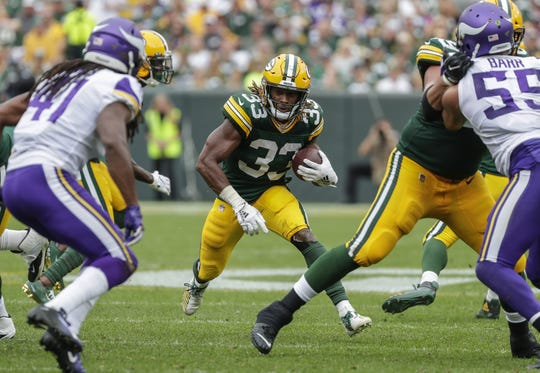 Green Bay Packers running back Aaron Jones (33) runs the ball against the Minnesota Vikings during their football game Sunday, September 15, 2019, at Lambeau Field in Green Bay, Wis.