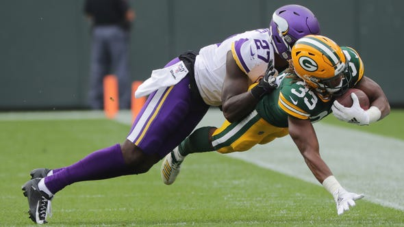 Green Bay Packers running back Aaron Jones (33) stretches for a first down before being knocked out of bounds by safety Jayron Kearse (27) during the first quarter of their game Sunday. September 15, 2019 at Lambeau Field in Green Bay, Wis.