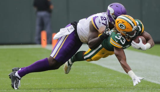 Packers running back Aaron Jones (33) stretches for a first down before being knocked out of bounds by Vikings safety Jayron Kearse (27) during the first quarter of Sunday's game at Lambeau Field.