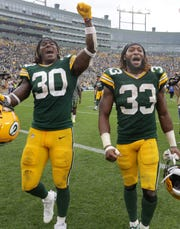 Green Bay Packers running back Jamaal Williams (30) and Green Bay Packers' Aaron Jones (33) leave the field following the Packers' victory over the Minnesota Vikings during their football game Sunday, August 15, 2019, at Lambeau Field in Green Bay, Wis.