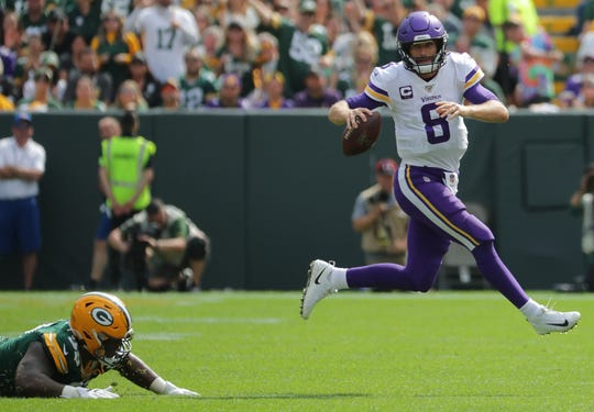 Minnesota Vikings quarterback Kirk Cousins (8) eludes a sack by Green Bay Packers nose tackle Kenny Clark (97) during the third quarter of their game Sunday. September 15, 2019 at Lambeau Field in Green Bay, Wis. The Green Bay Packers beat the Minnesota Vikings 21-16.