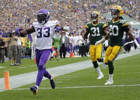 Vikings running back Dalvin Cook (33) scores a touchdown against Packers defensive backs Adrian Amos (31) and Kevin King (20) during their Sept. 15 game at Lambeau Field.