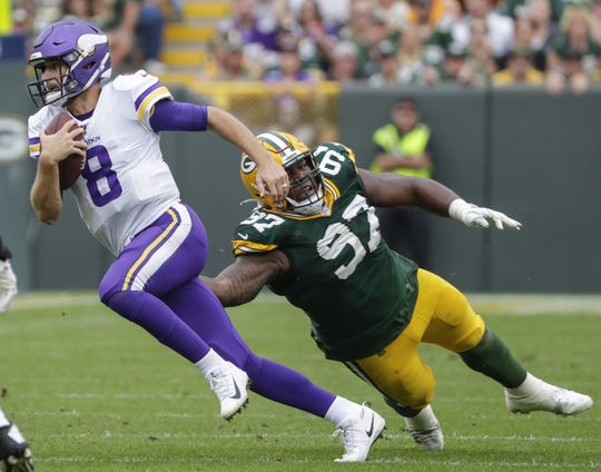 Minnesota Vikings quarterback Kirk Cousins (8) scrambles from Green Bay Packers nose tackle Kenny Clark (97) during their football game Sept. 15, 2019, at Lambeau Field in Green Bay, Wis.