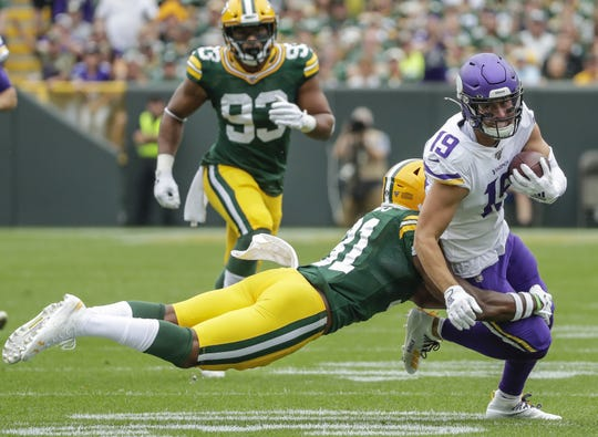Green Bay Packers strong safety Adrian Amos (31) brings down Minnesota Vikings wide receiver Adam Thielen (19) during their football game Sunday, September 15, 2019, at Lambeau Field in Green Bay, Wis.