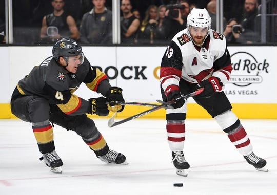 Sep 15, 2019; Las Vegas, NV, USA; Vegas Golden Knights defenseman Jimmy Schuldt (4) ties up the stick of Arizona Coyotes right wing Vinnie Hinostroza (13) during the third period of a preseason game at T-Mobile Arena. Mandatory Credit: Stephen R. Sylvanie-USA TODAY Sports
