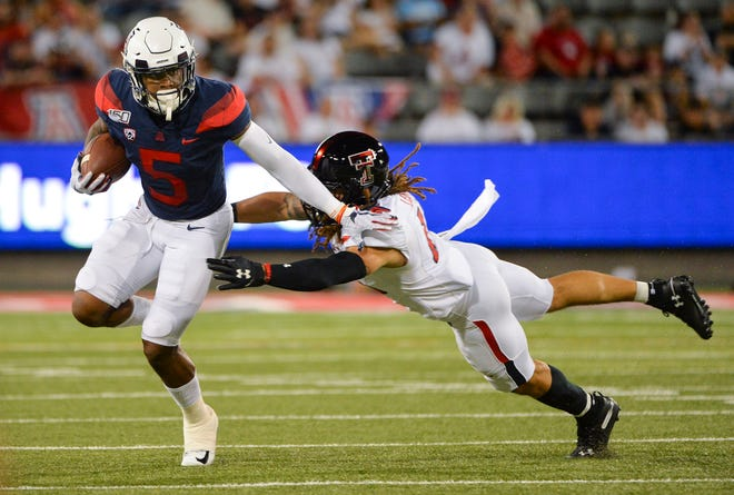 Sep 14, 2019; Tucson, AZ, USA; Arizona Wildcats wide receiver Brian Casteel (5) is tackled by Texas Tech Red Raiders defensive back Thomas Leggett (16) during the first half at Arizona Stadium. Mandatory Credit: Casey Sapio-USA TODAY Sports