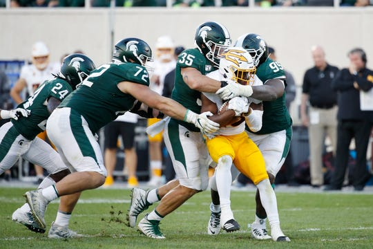 Joe Bachie (35) and Raequan Williams (99) of the Michigan State Spartans tackle Eno Benjamin (3) of the Arizona State Sun Devils in the second half of the game at Spartan Stadium on September 14, 2019 in East Lansing, Michigan. Arizona State defeated Michigan State 10-7.