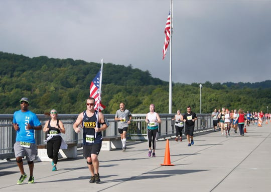 Jeremy Lucca of Suffern carries an American Flag while running over the Walkway Over The Hudson during the 41st Dutchess County Classic in the City of Poughkeepsie on September 15, 2019.