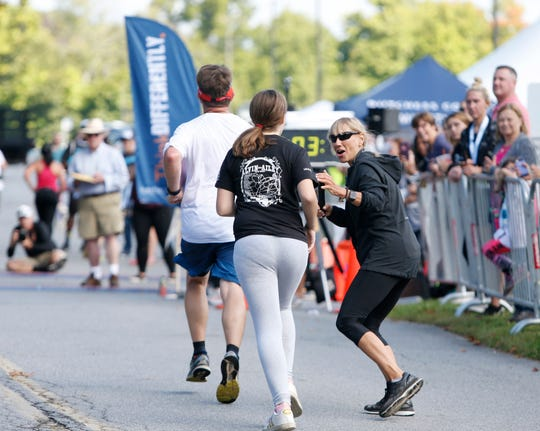 Lori Decker from the Mid-Hudson Road Runners cheers on runners as they near the finish line during the 41st Dutchess County Classic in the Town of Poughkeepsie on September 15, 2019.