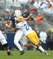 Penn State quarterback Sean Clifford loses the ball as he is hit by Pitt linebacker Phil Campbell III.