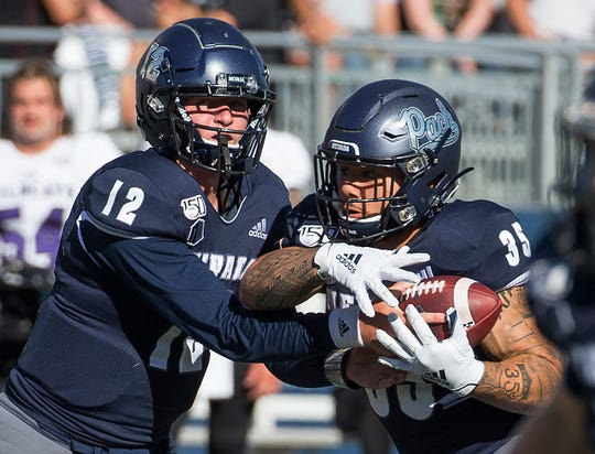 Nevada's quarterback Carson Strong (12) hands the ball off to Toa Taua (35) during the Nevada vs Weber State football game in Reno, Nevada on Saturday, Sept. 14, 2019.