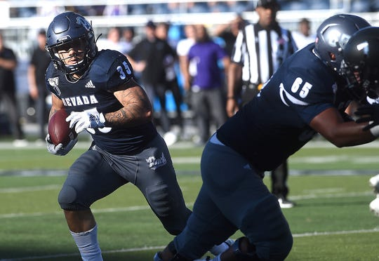 Nevada's Toa Taua runs against Weber State on Saturday.