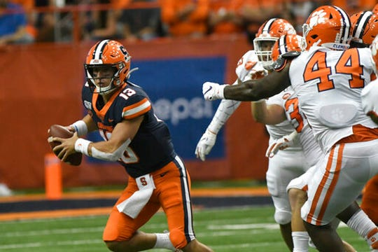 Syracuse quarterback Tommy Devito, left, scrambles away from the Clemson defense during the first half of an NCAA college football game Saturday, Sept. 14, 2019, in Syracuse, N.Y. (