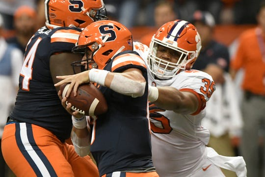 Clemson's Justin Foster, right, rushes Syracuse quarterback Tommy DeVito during the first half of an NCAA college football game Saturday, Sept. 14, 2019, in Syracuse, N.Y.