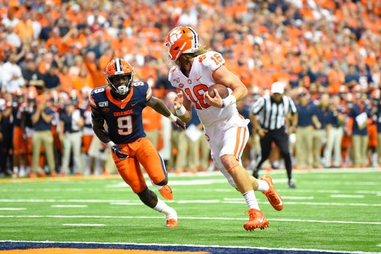 Clemson Tigers quarterback Trevor Lawrence (16) looks back at Syracuse Orange defensive back Evan Foster (9) while running into the end zone for a touchdown during the first quarter at the Carrier Dome.