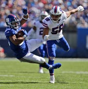 New York Giants' Saquon Barkley, left, is tackle by Buffalo Bills' Matt Milano during the first half of an NFL football game, Sunday, Sept. 15, 2019, in East Rutherford, N.J. (AP Photo/Adam Hunger)