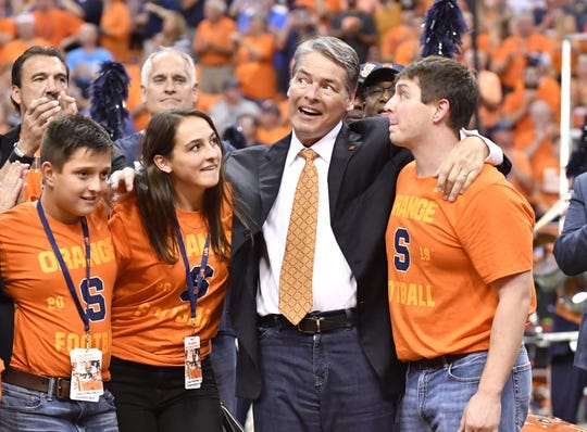 Former Syracuse Orange player Tim Green surrounded by his family smiles at the crowd during a halftime ceremony to retire his number 72 jersey at the Carrier Dome.