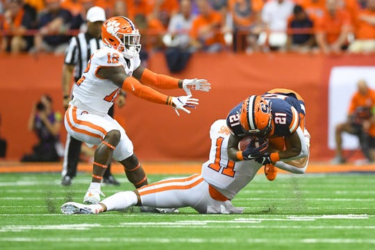Syracuse Orange running back Moe Neal (21) is tackled by Clemson Tigers linebacker Isaiah Simmons (11) on a run during the first quarter at the Carrier Dome.