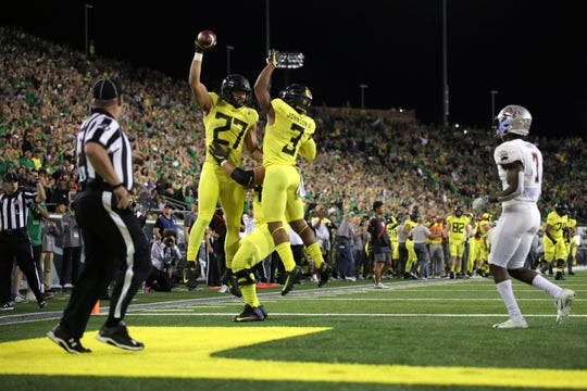 Sep 14, 2019; Eugene, OR, USA; Oregon tight end Jacob Breeland (27) celebrates Oregon's first touchdown with right tackle Calvin Throckmorton (54), behind, and wide receiver Johnny Johnson III (3) as Montana center back Dareon Nash (7) slows down following the play at Autzen Stadium. Mandatory Credit: Rob Kerr-USA TODAY Sports