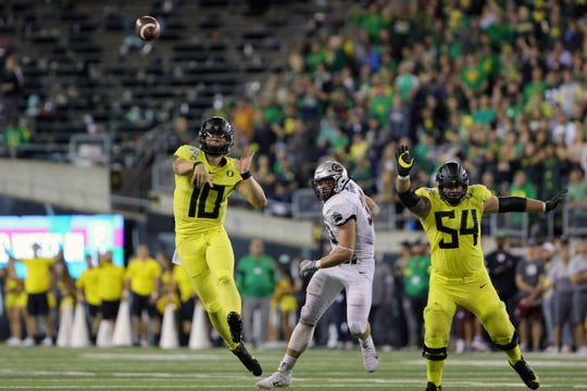 Sep 14, 2019; Eugene, OR, USA; Oregon quarterback Justin Herbert (10) throws a second quarter touchdown pass to wide receiver Johnny Johnson III (3) , not pictured, with pressure from Montana linebacker Dante Olson (33) and help from Oregon right tackle Calvin Throckmorton (54) against Montana at Autzen Stadium. Mandatory Credit: Rob Kerr-USA TODAY Sports