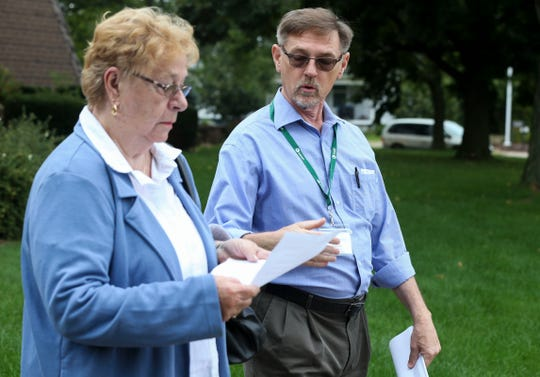 Missouri director and former national director of the Survivors Network of those Abused by Priests David Clohessy, of St. Louis, gives a flier with information about credibly accused priests to a parishioner on Sunday, September 15, 2019, at St. Michael's Catholic Church in Wausau, Wis.  Tork Mason/USA TODAY NETWORK-Wisconsin