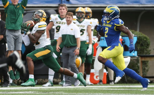 North Dakota State's Phoenix Sproles (left) grabs a pass good for 41 yards in the second quarter as Delaware's Tim Poindexter defends at Delaware Stadium Saturday.