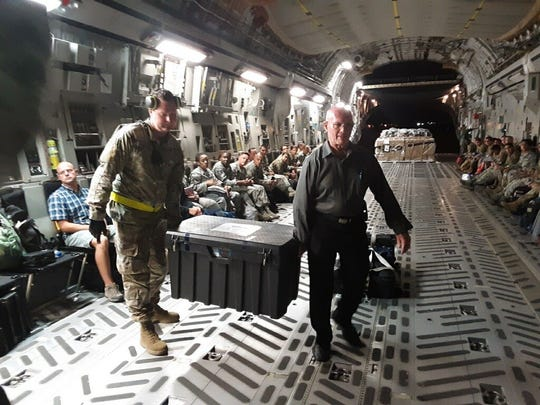 A U.S. Air Force flight carrying the remains of the 81 South Vietnamese soldiers arrives in Southern California on Sept. 13, 2019. They were escorted by retired Col. Gene (Gino) Castagnetti, right, former director of the National Memorial Cemetery of the Pacific, to a mortuary in Westminster, California.