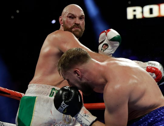 Tyson Fury, left, takes a swing at Otto Wallin.